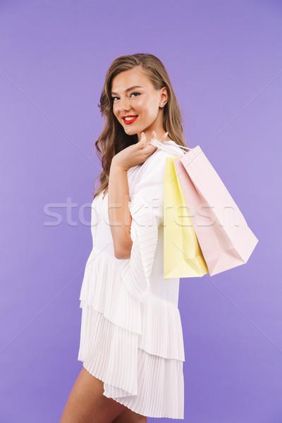 Portrait of shopaholic woman 20s wearing white dress holding pap Stock photo © deandrobot
