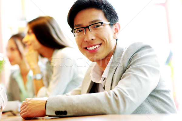 Portrait of smiling businessman sitting in front of colleagues Stock photo © deandrobot