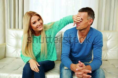 Young man covering his girlfriend`s eyes Stock photo © deandrobot