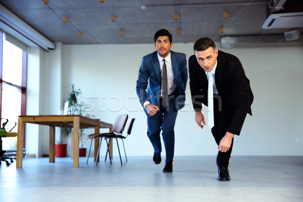 Two businessman running together in office. Business concept Stock photo © deandrobot