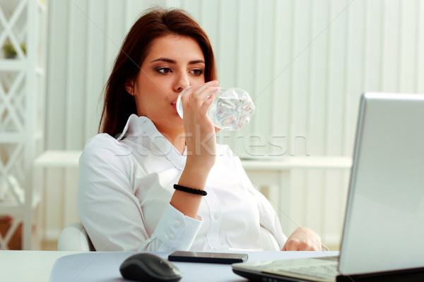 Stock photo: Young businesswoman drinks water on her workplace in office