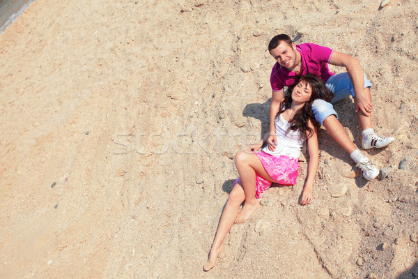 happy young love couple sitting on the beach. Stock photo © deandrobot