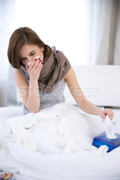 Sick Woman. flu. woman caught cold. sneezing into tissue Stock photo © deandrobot