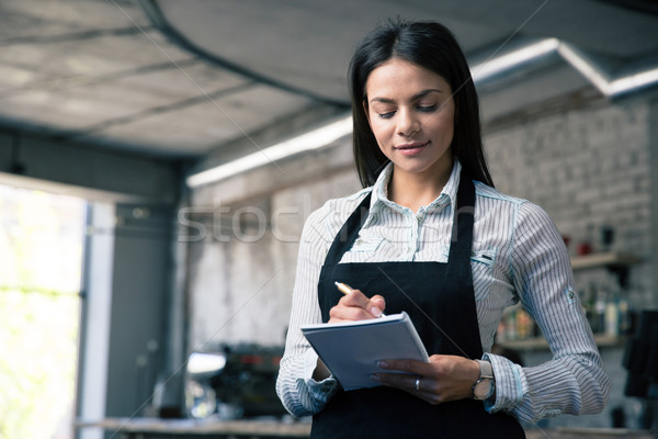 Female waiter in apron writing order Stock photo © deandrobot