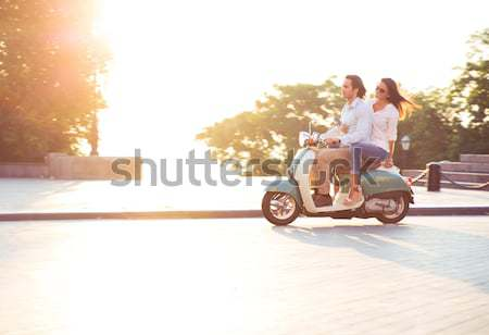 Happy young couple riding a scooter outdoors Stock photo © deandrobot