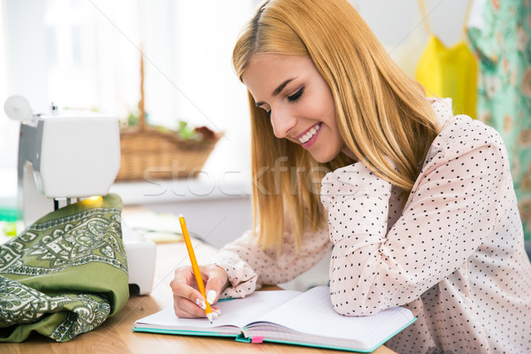 Stock photo: Happy female tailor writing notes