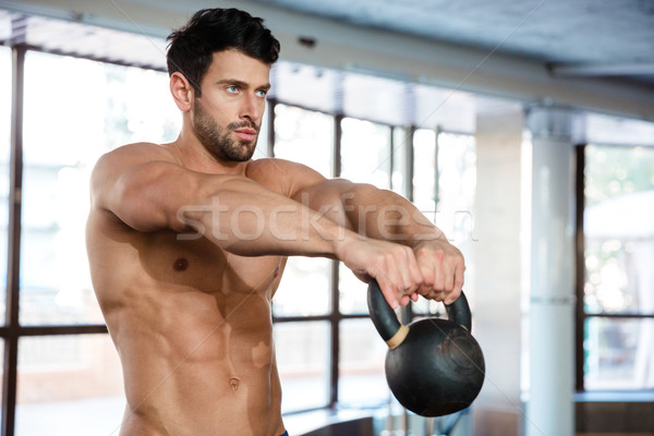 Muscular man workout with kettle ball  Stock photo © deandrobot