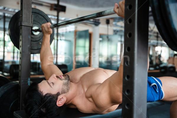 élégant Homme bodybuilder banc presse portrait Photo stock © deandrobot