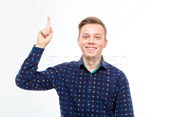 Cheerful attractive young blond man in checkered shirt pointing up Stock photo © deandrobot