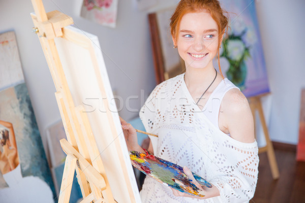 Woman painter holding palette with oil paints in art studio Stock photo © deandrobot
