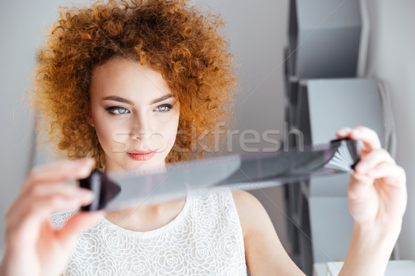 Attractive curly young female photographer looking at photographic film  Stock photo © deandrobot