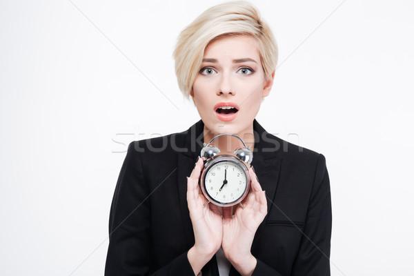Charming businesswoman holding alarm clock Stock photo © deandrobot