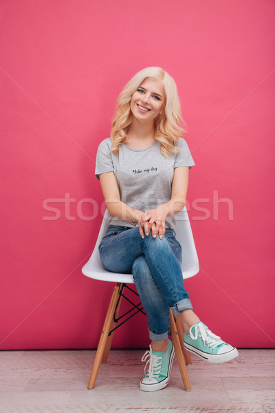 Smiling pretty woman sitting on the chair Stock photo © deandrobot
