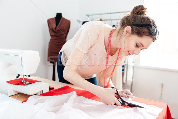 Focused woman fashion designer cutting white fabric in studio Stock photo © deandrobot