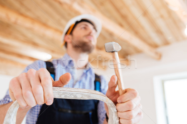 Close-up portrait of pensive worker with a hammer Stock photo © deandrobot