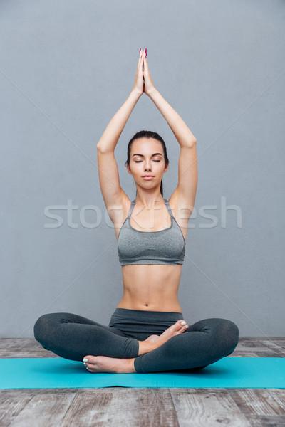 Young woman doing yoga exercise Padmasana (Lotus Pose) Stock photo © deandrobot