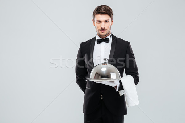 Waiter in tuxedo holding serving tray with cloche and napkin Stock photo © deandrobot