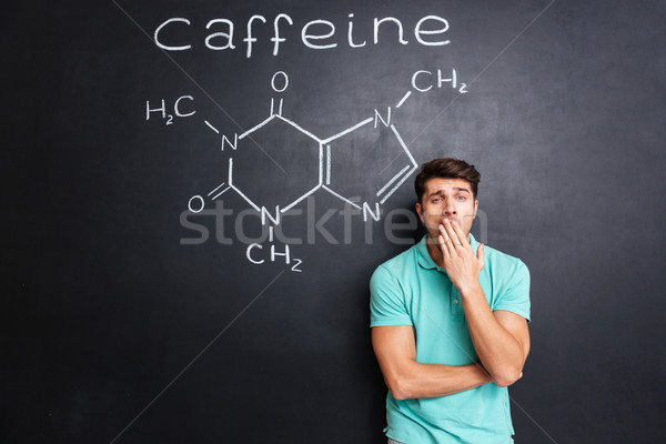 Tired sleepy man yawning over blackboard with drawn caffeine molecule Stock photo © deandrobot