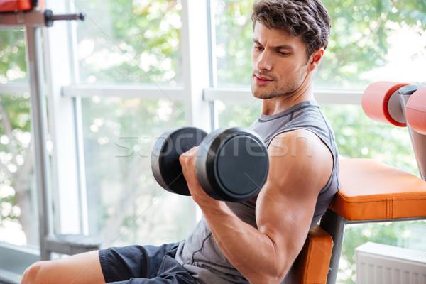 Stock photo: Sportsman doing exercises for biceps using dumbbells in jym