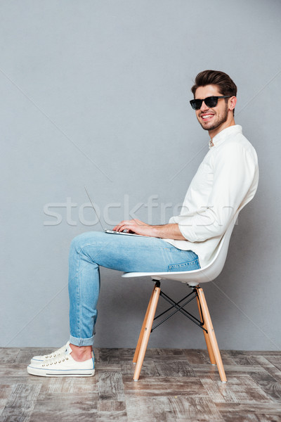 Cheerful man in sunglasses sitting on chair and using laptop Stock photo © deandrobot