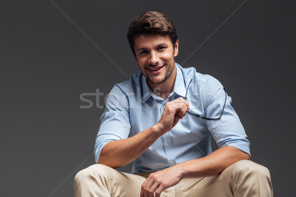 Happy young smiling man holding sunglasses and sitting Stock photo © deandrobot