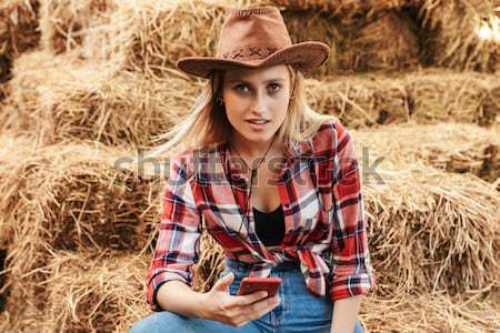 Smiling cowgirl using mobile phone while standing at ranch fence Stock photo © deandrobot