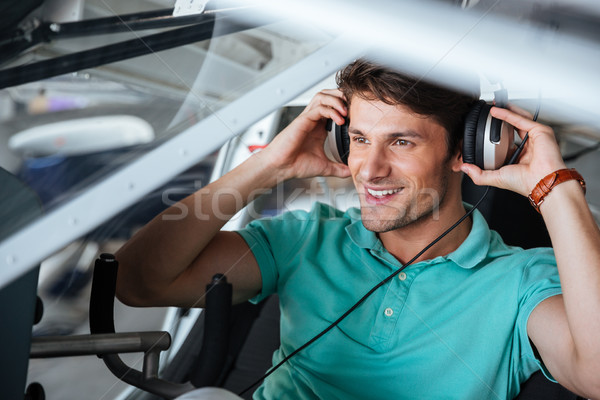 Happy man pilot sitting in cabin of small plane Stock photo © deandrobot