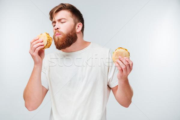 Eccitato barbuto uomo mangiare Foto d'archivio © deandrobot