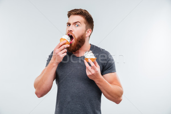 Attractive bearded man biting cream cake Stock photo © deandrobot