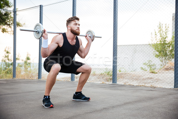 Concentrated bearded sports man doing squatting exercises with barbell Stock photo © deandrobot
