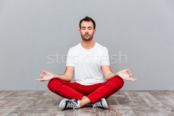 Man in casual cloth sitting in lotus position Stock photo © deandrobot