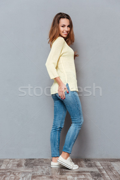 Stock photo: Smiling casual woman standing and looking at camera