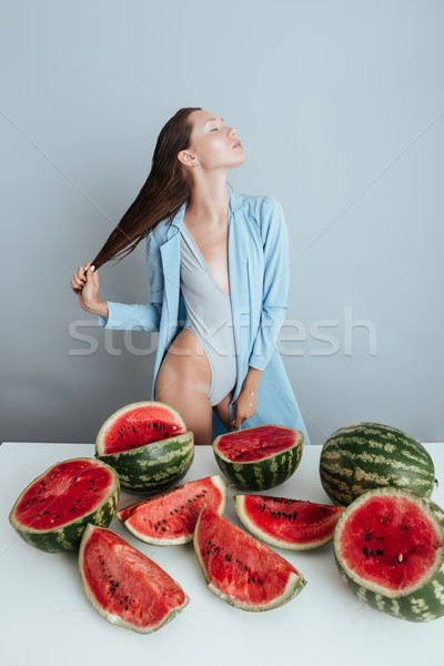 Seductive young woman near the table with cutted watermelons Stock photo © deandrobot