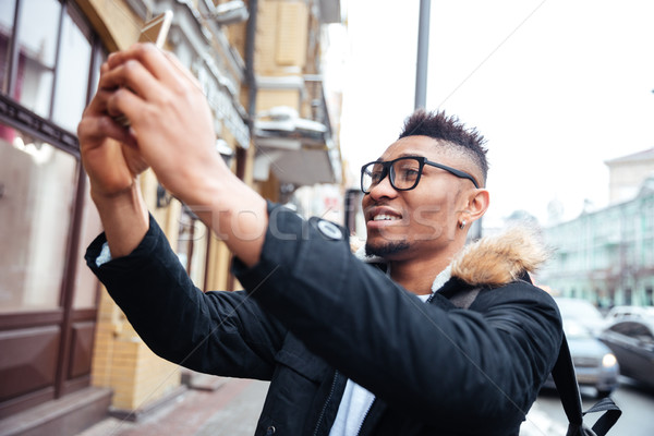 African happy man make a selfie outdoors. Stock photo © deandrobot