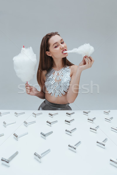 Woman eating cotton candy at the table with razor blades Stock photo © deandrobot