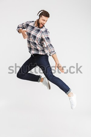Casual young man in plaid shirt jumping in the air Stock photo © deandrobot
