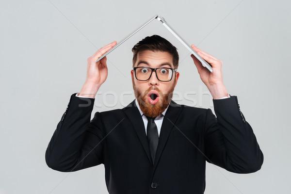 Business man holding laptop overhead Stock photo © deandrobot