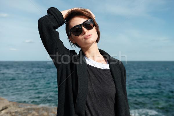 Mulher óculos de sol preto jaqueta em pé beira-mar Foto stock © deandrobot