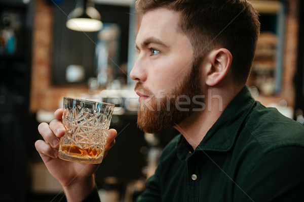 Young man sitting and drinking whiskey Stock photo © deandrobot