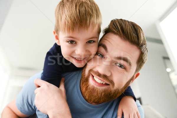 Cheerful bearded father playing with his little cute son indoors Stock photo © deandrobot