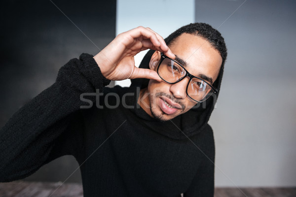 Portrait of handsome african young man in hoodie and glasses Stock photo © deandrobot