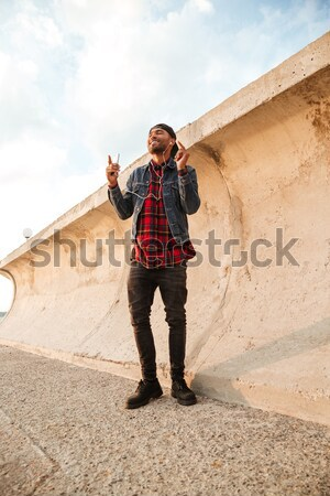 Cheerful man with arms spread opened standing at the beach Stock photo © deandrobot