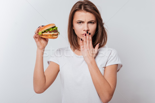 Angry woman holding fastfood and covering mouth Stock photo © deandrobot