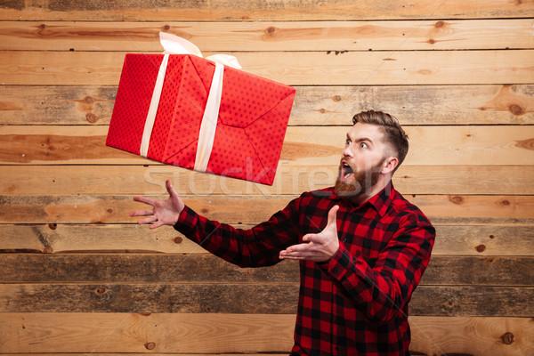 Fiatal szakállas férfi zsákmány ajándék doboz mozgás Stock fotó © deandrobot