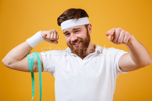 Sports man measuring his biceps and pointing finger at camera Stock photo © deandrobot