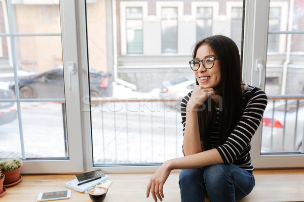 Front view of Asian woman sitting on windowsill Stock photo © deandrobot