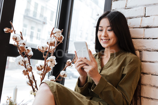 Stock photo: Smiling asian young woman chatting by her mobile phone