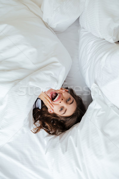Emotional young lady lies in bed at home under a blanket Stock photo © deandrobot