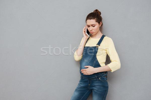 Zmartwiony młodych kobieta w ciąży mówić telefonu komórkowego depresji Zdjęcia stock © deandrobot