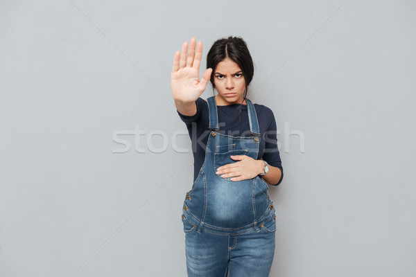 Serious pregnant lady make stop gesture Stock photo © deandrobot